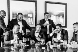 Groom and groomsmen joking over drinks.