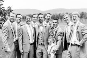 The groom, groomsmen, and the ring bearer pose for an outdoor shot.