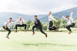 Groom and groomsmen jumping in the air in unison