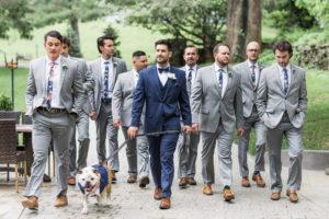 Groom walking his dog with his groomsmen.