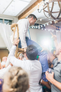 Groom being held up by a chair