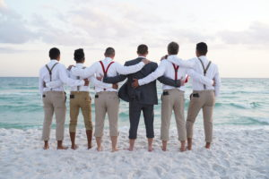 The groom with his groomsmen standing on the beach looking out at the water.