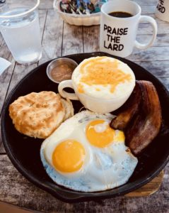 "Fried eggs, bacon, a biscuit, and cheese grits, served in a skilled with coffee in a ""Praise the Lard"" mug"